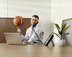 Businessman balancing basketball on finger while working